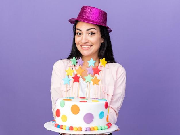 Glimlachend jong mooi meisje met feestmuts die cake uitstak naar de camera
