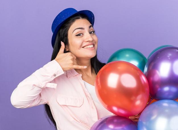 Glimlachend jong mooi meisje met feestmuts met ballonnen die een telefoongesprekgebaar tonen