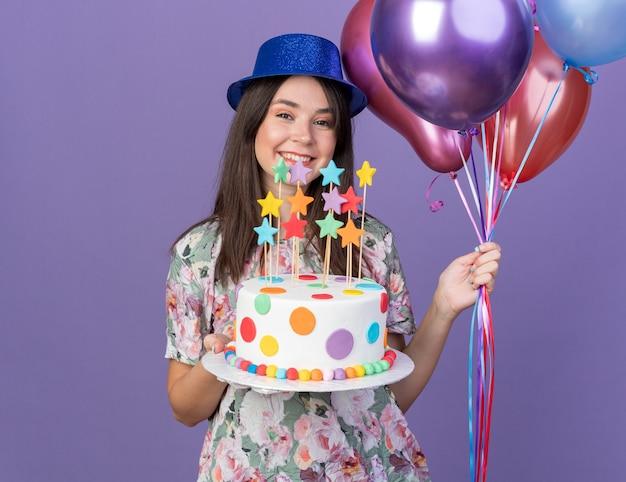 Glimlachend jong mooi meisje met feestmuts met ballonnen met cake geïsoleerd op blauwe muur