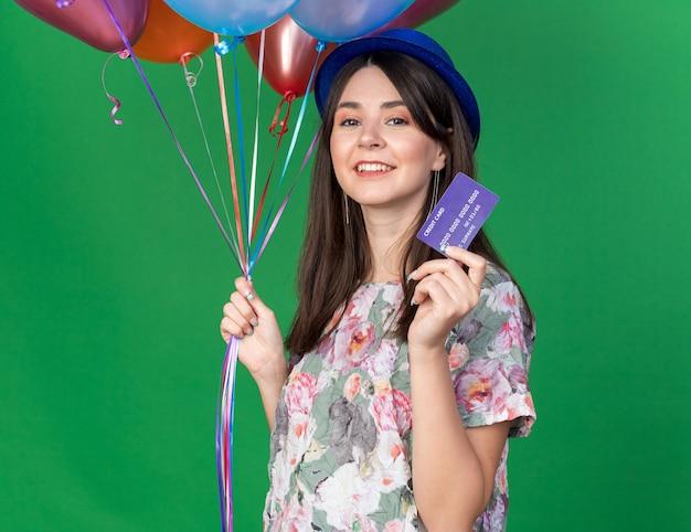 Glimlachend jong mooi meisje met feestmuts met ballonnen met creditcard