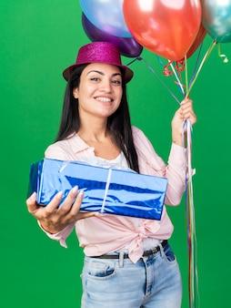 Glimlachend jong mooi meisje met feestmuts met ballonnen met geschenkdoos