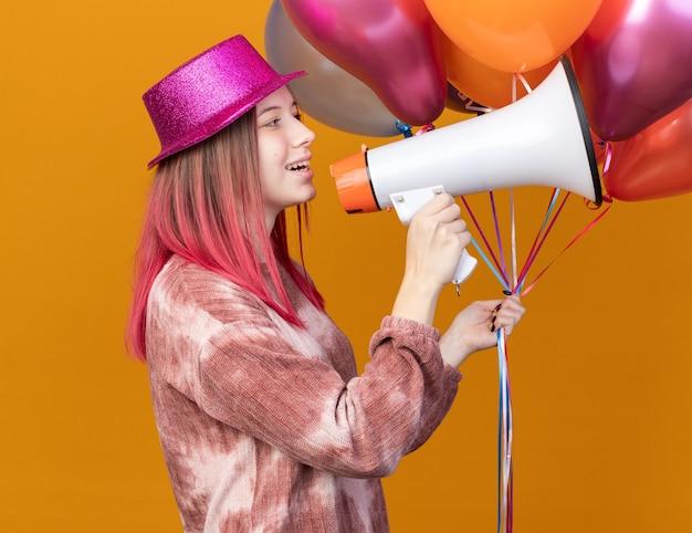 Glimlachend jong mooi meisje met feestmuts met ballonnen spreekt op luidspreker
