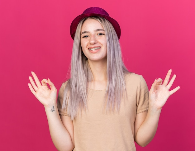 Glimlachend jong mooi meisje met feestmuts met beugels die meditatie doen Premium Foto