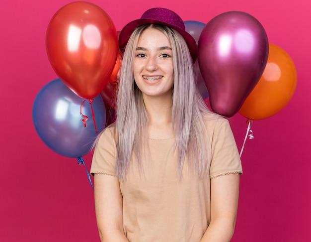 Glimlachend jong mooi meisje met feestmuts met beugels die voor ballonnen staan