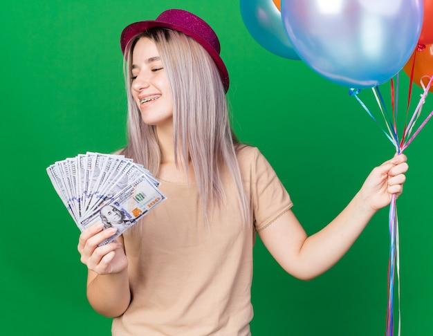 Glimlachend jong mooi meisje met feestmuts met bretels die ballonnen vasthoudt en contant geld naar de camera steekt