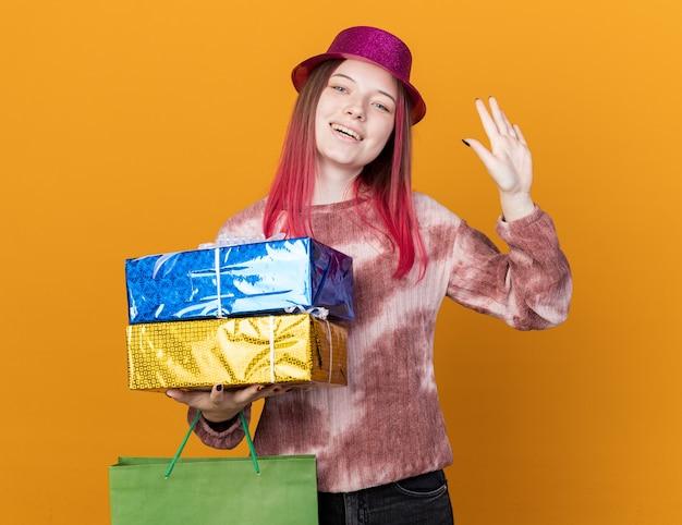 Glimlachend jong mooi meisje met feestmuts met cadeauzakje met geschenkdozen met hallo gebaar geïsoleerd op oranje muur