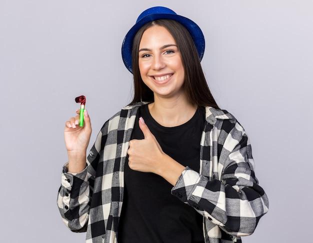 Glimlachend jong mooi meisje met feestmuts met feestfluitje dat duim omhoog laat zien