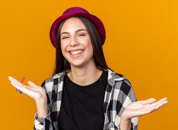 Glimlachend jong mooi meisje met feestmuts met feestfluitje en spreidende hand geïsoleerd op oranje muur