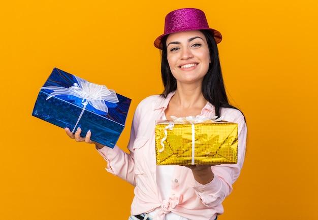 Glimlachend jong mooi meisje met feestmuts met geschenkdozen geïsoleerd op een oranje muur