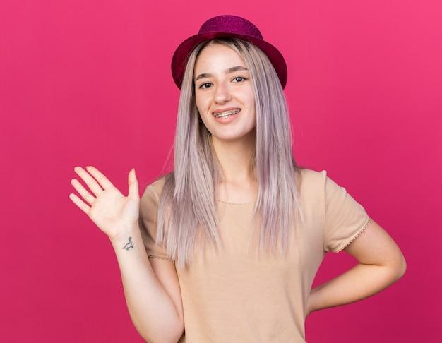 Glimlachend jong mooi meisje met feestmuts met tandheelkundige beugels met hallo gebaar geïsoleerd op roze muur