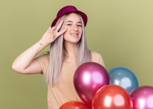Glimlachend jong mooi meisje met gebitsbeugels met feestmuts die achter ballonnen staat en vredesgebaar toont