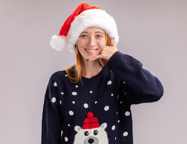 Glimlachend jong mooi meisje met kerstmuts die een telefoongesprekgebaar toont dat op een witte muur wordt geïsoleerd