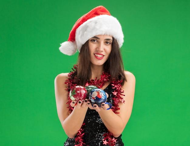 Glimlachend jong mooi meisje met kerstmuts met guirlande op nek die kerstboomballen uithoudt op camera geïsoleerd op groene achtergrond