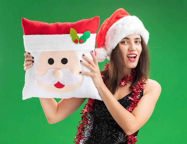 Glimlachend jong mooi meisje met kerstmuts met slinger op nek kerst kussen geïsoleerd op groene muur te houden