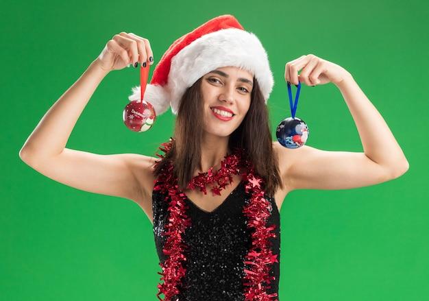 Glimlachend jong mooi meisje met kerstmuts met slinger op nek met kerstboom ballen geïsoleerd op groene muur