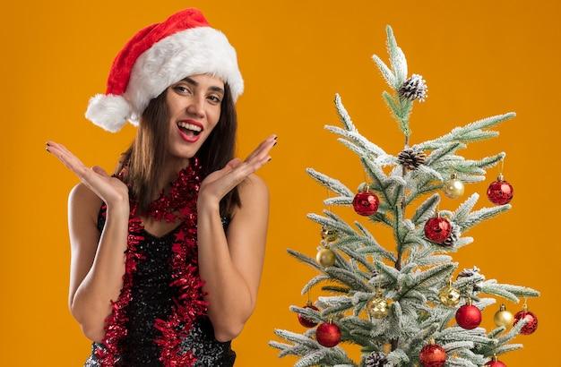 Glimlachend jong mooi meisje met kerstmuts met slinger op nek staande in de buurt van kerstboom hand in hand rond gezicht geïsoleerd op een oranje achtergrond
