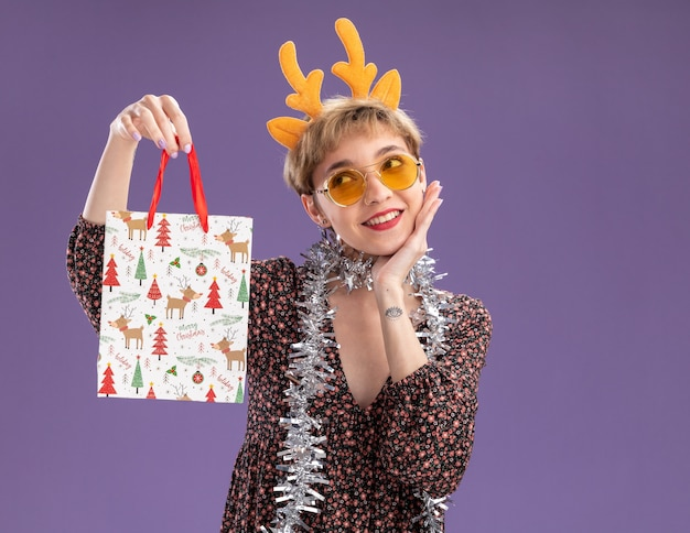 Glimlachend jong mooi meisje met rendiergeweien hoofdband en klatergoudslinger om nek met bril met kerstcadeauzakje met hand op gezicht kijkend naar kant geïsoleerd op paarse muur met kopieerruimte