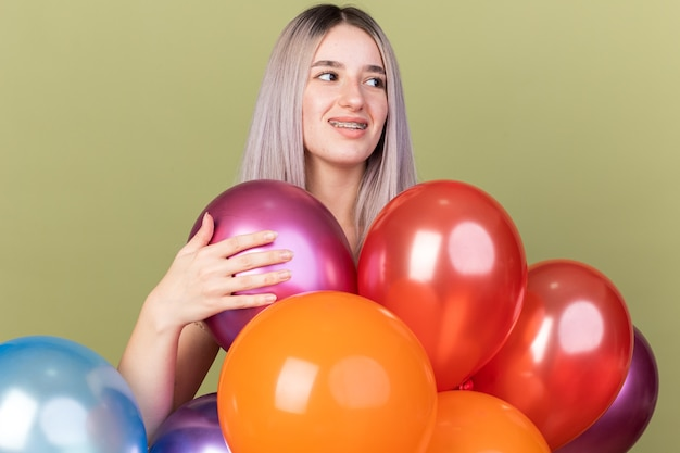 Glimlachend jong mooi meisje met tandheelkundige beugels die achter ballonnen staan geïsoleerd op olijfgroene muur