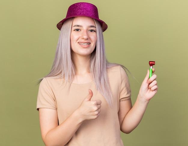 Glimlachend jong mooi meisje met tandheelkundige beugels met feestmuts die een fluitje vasthoudt met duim omhoog geïsoleerd op olijfgroene muur
