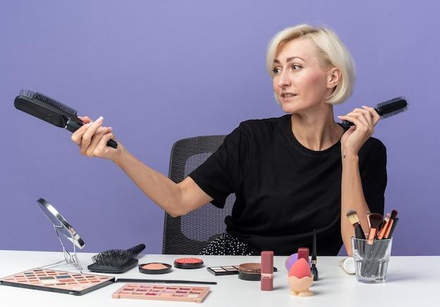 Glimlachend jong mooi meisje zit aan tafel met make-uptools die kammen uitstrekken aan de zijkant geïsoleerd op blauwe achtergrond