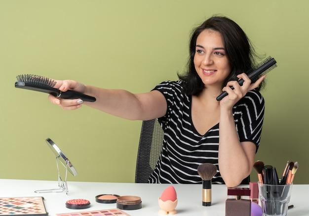 Glimlachend jong mooi meisje zit aan tafel met make-uptools die kammen uitstrekken aan de zijkant geïsoleerd op olijfgroene achtergrond