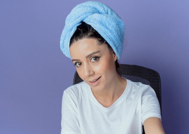 Glimlachend jong mooi meisje zittend aan make-up tafel met make-up tools en met badhanddoek op hoofd kijken naar camera geïsoleerd op paarse achtergrond