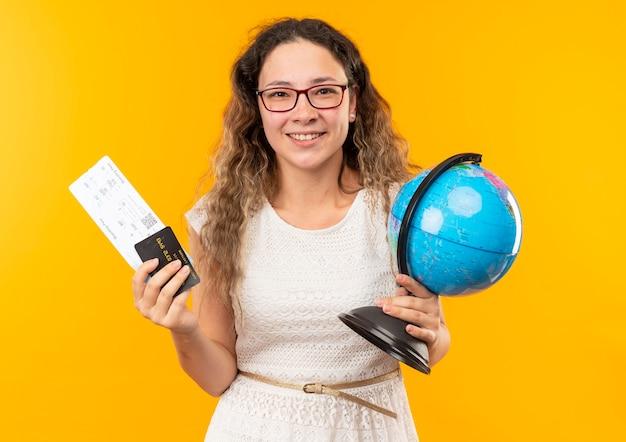 Glimlachend jong mooi schoolmeisje die glazen dragen die vliegtuigkaartjes, creditcard en bol houden die op gele muur worden geïsoleerd