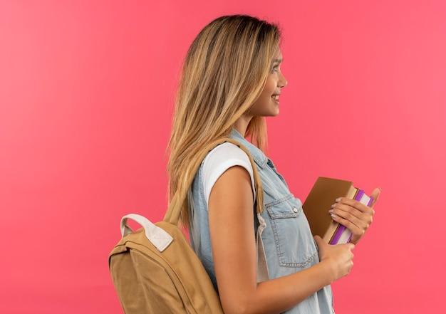 Glimlachend jong mooi studentenmeisje die achterzak dragen die zich in de holdingsboeken van de profielmening bevinden die op roze muur worden geïsoleerd
