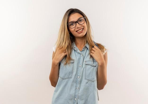 Glimlachend jong mooi studentenmeisje die glazen en de riemen van de achterzakholding van achterzak dragen die op witte muur wordt geïsoleerd
