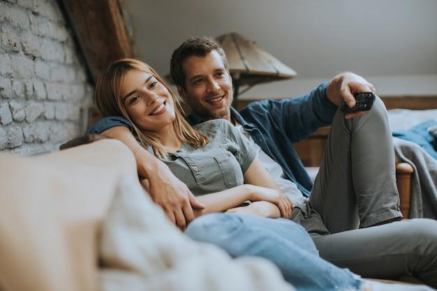 Glimlachend jong paar dat en op tv thuis ontspant let