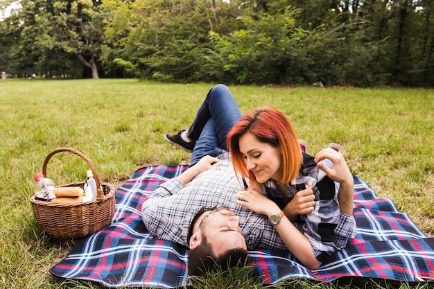Glimlachend jong paar die op deken over groen gras bij picknick liggen