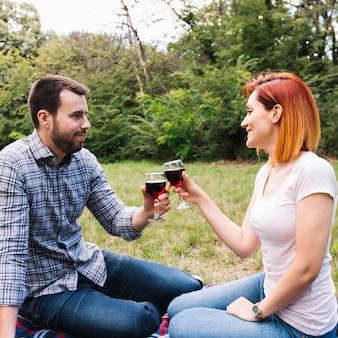 Glimlachend jong paar die wijnglazen roosteren die in het park zitten