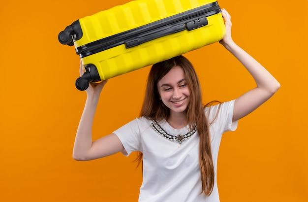 Glimlachend jong reizigersmeisje die koffer op hoofd zetten op geïsoleerde oranje muur