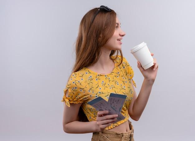 Glimlachend jong reizigersmeisje die vliegtuigtickets en plastic koffiekop bekijken die rechterkant op geïsoleerde witte muur met exemplaarruimte bekijken