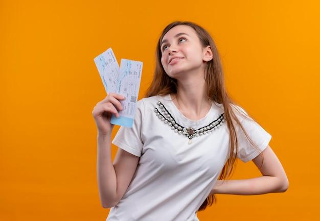Glimlachend jong reizigersmeisje die vliegtuigtickets houden en hand op taille zetten die omhoog op geïsoleerde oranje muur met exemplaarruimte kijken