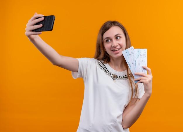 Glimlachend jong reizigersmeisje die vliegtuigtickets houden en selfie op geïsoleerde oranje muur nemen
