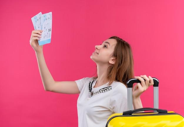 Glimlachend jong reizigersmeisje met vliegtuigtickets en koffer die omhoog op geïsoleerde roze muur kijken