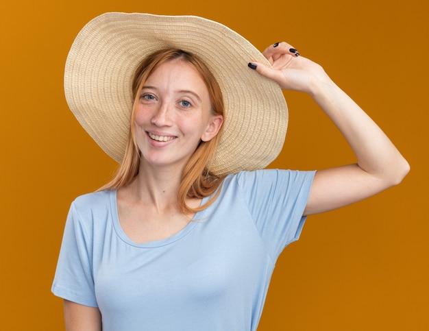 Glimlachend jong roodharig gembermeisje met sproeten die een strandhoed dragen en vasthouden, geïsoleerd op een oranje muur met kopieerruimte