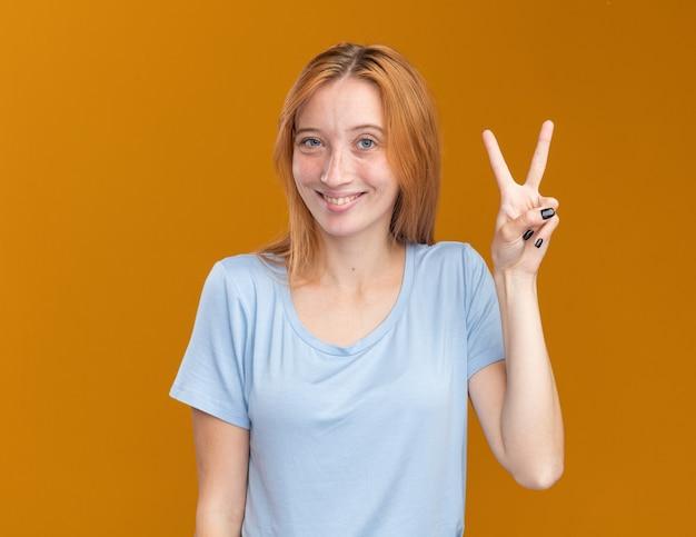 Glimlachend jong roodharig gembermeisje met sproeten gebaren overwinningsteken geïsoleerd op oranje muur met kopieerruimte