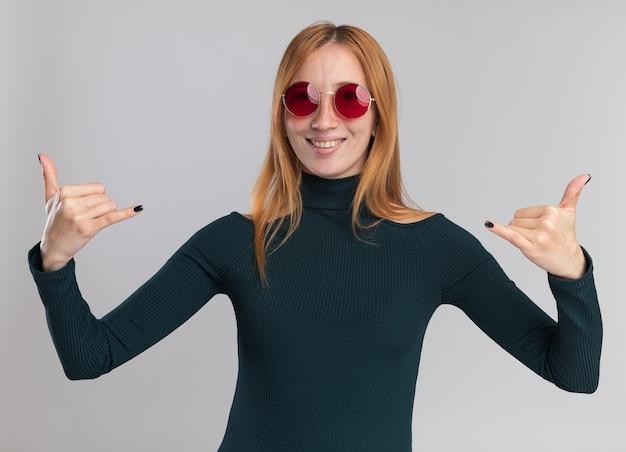 Glimlachend jong roodharige gember meisje met sproeten in zonnebril doen hangen los gebaar met twee handen geïsoleerd op een witte muur met kopie ruimte