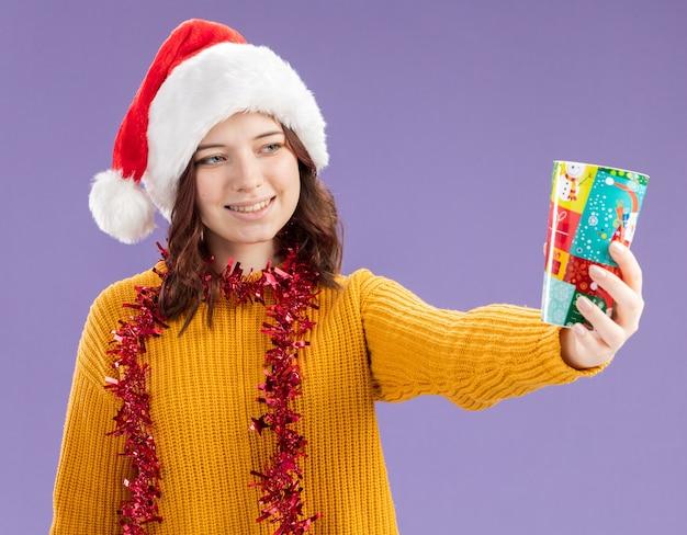 Glimlachend jong slavisch meisje met kerstmuts en met slinger om de nek houden en kijken naar papieren beker geïsoleerd op paarse achtergrond met kopie ruimte