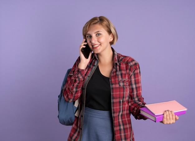 Glimlachend jong slavisch studentenmeisje dat een rugzak draagt, houdt boek- en notitieboekjes aan de telefoon