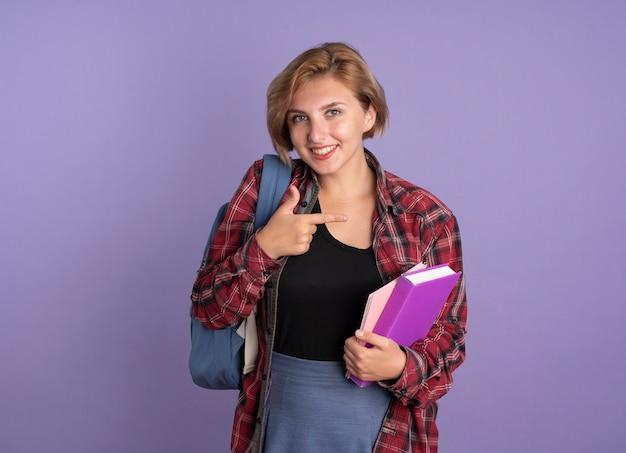 Glimlachend jong slavisch studentenmeisje dat een rugzak draagt met een boek en een notitieboekje dat naar de zijkant wijst