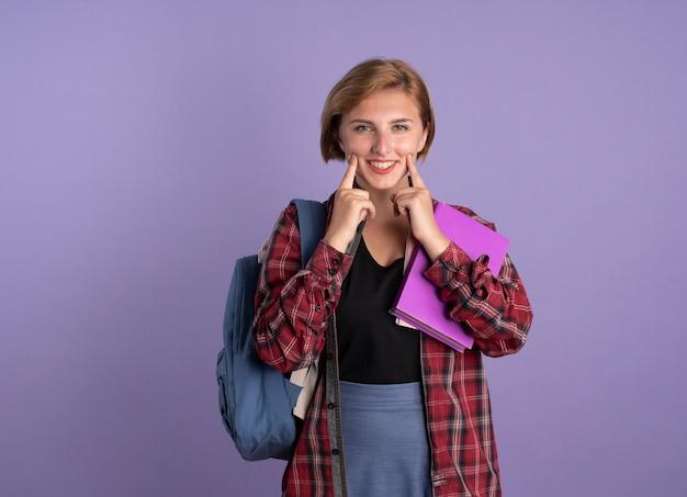 Glimlachend jong slavisch studentenmeisje dat rugzak draagt, blijft glimlachen met vingers met boek en notitieboekje