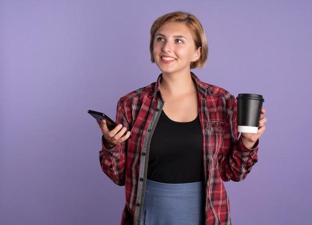 Glimlachend jong slavisch studentenmeisje houdt telefoon en beker vast en kijkt naar de zijkant