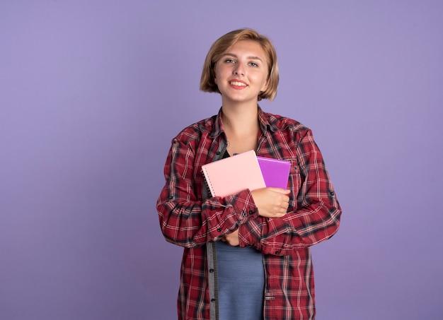 Glimlachend jong slavisch studentenmeisje met boek en notitieboekje