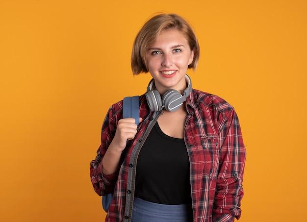 Glimlachend jong slavisch studentenmeisje met een koptelefoon die een rugzak draagt, kijkt naar de camera