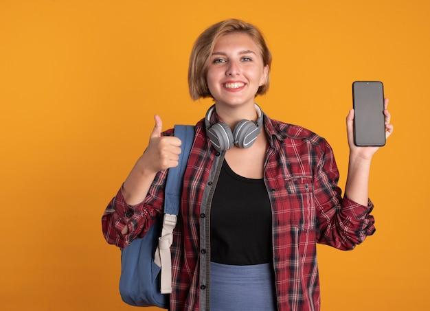 Glimlachend jong slavisch studentenmeisje met koptelefoon die rugzak draagt, houdt telefoon en duimen omhoog