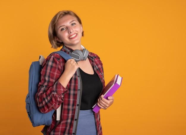 Glimlachend jong slavisch studentenmeisje met koptelefoon die rugzak draagt, staat zijwaarts met boek en notitieboekje