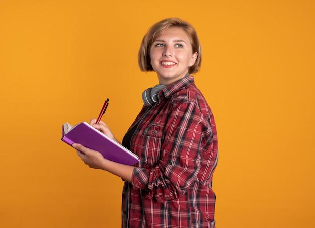 Glimlachend jong slavisch studentenmeisje met koptelefoon die rugzak draagt, staat zijwaarts met boek en pen